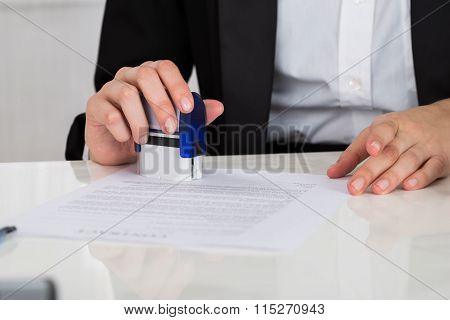Businesswoman Stamping Contract Document At Desk
