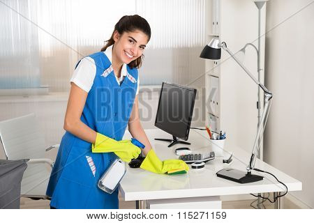 Worker Cleaning Computer Desk With Spray And Sponge
