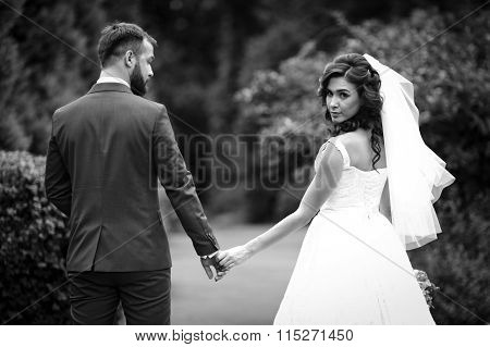 Happy Couple , Bride And Groom, Holding Hands In A Garden B&w
