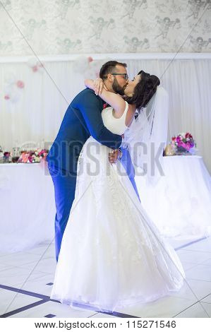 Happy Newlywed Couple Kissing During Their First Dance At Wedding Reception