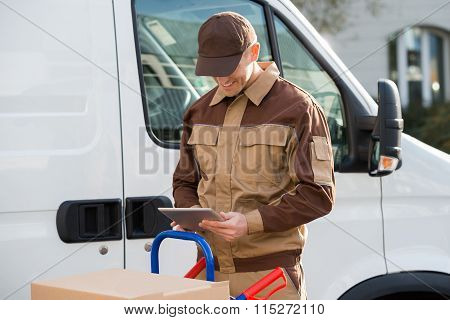 Smiling Delivery Man Holding Digital Tablet Against Truck