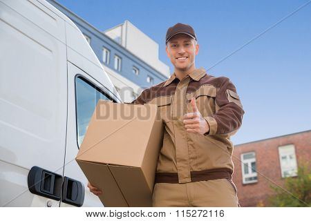 Man Carrying Cardboard Box While Gesturing Thumbs Up By Truck