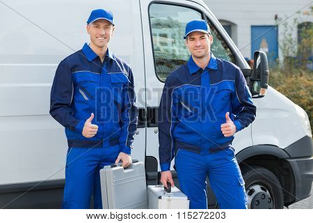 Happy Technicians Showing Thumbsup Against Truck