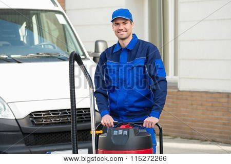 Confident Janitor Standing With Vacuum Cleaner