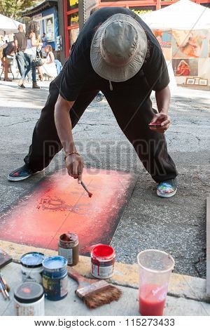 Artist Flicks Red Paint Onto Painting At Arts Festival