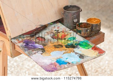 Artist Palette Covered With Oil Paints Sits Ready On Easel