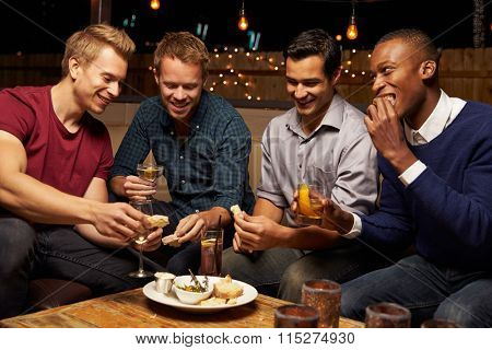 Group Of Male Friends Enjoying Night Out At Rooftop Bar
