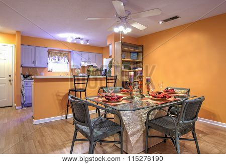 Open concept apartment with diningroom and kitchen and orange walls