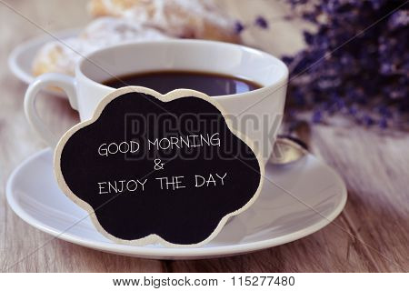 the text good morning and enjoy the day written in a thought bubble-shaped blackboard placed in a cup of coffee, with some pastries in the background in a set table for breakfast