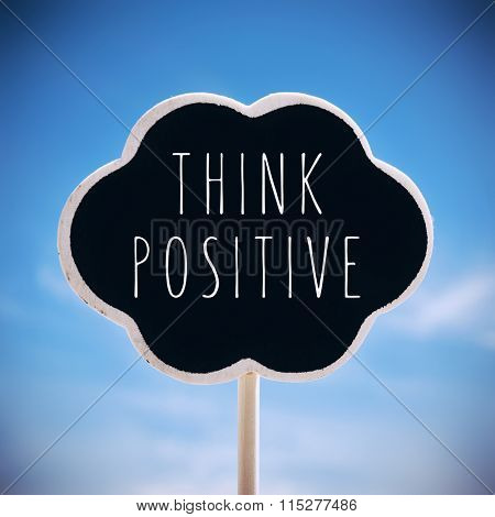 a chalkboard in the shape of a thought bubble with the text think positive written in it against the sky, with a slight vignette added