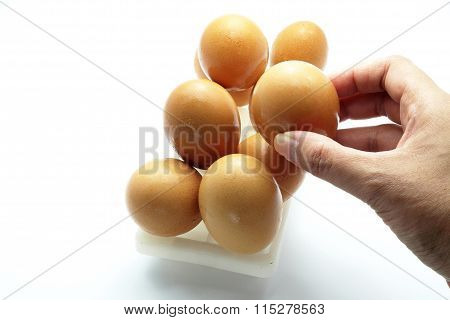 Egg in plastic cube with hand, isolated on white. Focus on an egg in hand
