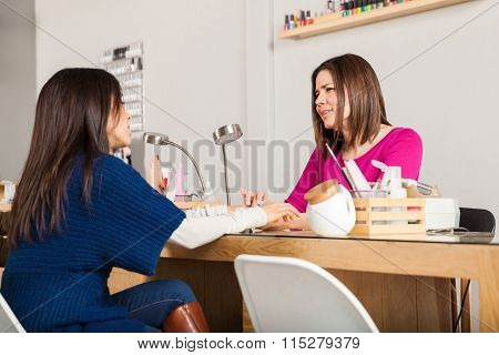 Manicurist And Client Talking In A Nail Salon