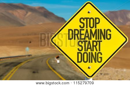Stop Dreaming Start Doing sign on desert road