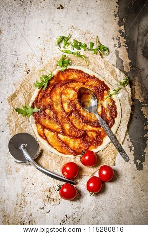 The Rolled Out Pizza Dough With Tomato Paste, Olive Oil And Tomatoes.