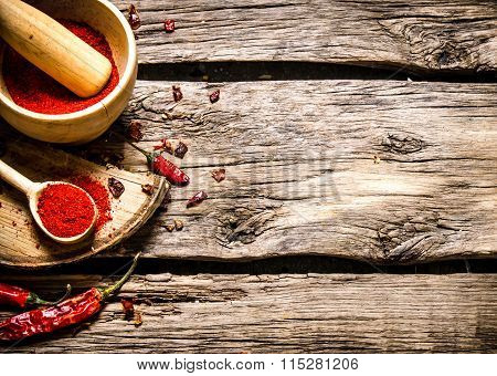 Ground Red Pepper In A Mortar And Spoon On A Birch Stand.