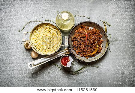 Spaghetti In Pan And Ground Beef In A Pan With Herbs And Olive Oil.