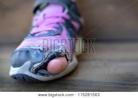 Old shoes with holes worn down shabby for homeless clothing toes sticking out