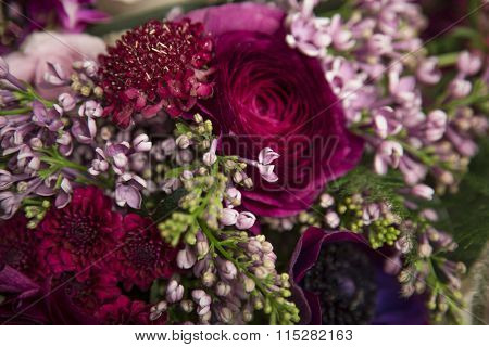 Beautiful close-up of a flower arrangement with purple and pink roses, peonies, anemones and lilac flowers
