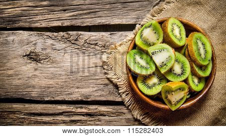 Sliced Kiwi Fruit In A Wooden Cup The Old Fabric.