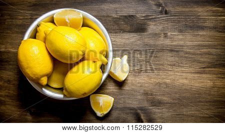 Lemons In A Cup . On Wooden Table.
