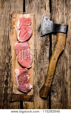 Medallions Of Raw Meat On A Tree With An Axe.