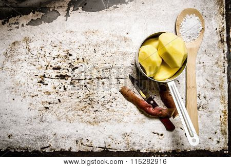 The Peeled Potatoes In A Metal Saucepan With A Spoonful Of Salt On The Rustic Background . Free Spac