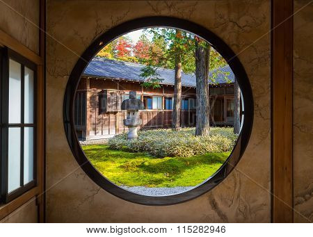 View of a Japanese Garden Through a Round Window  NIKKO JAPAN - NOVEMBER 16 2015: Tamozawa Imperial Villa first built in Tokyo in 1632. It was deconstructed and moved to the present location in Nikko in 1898