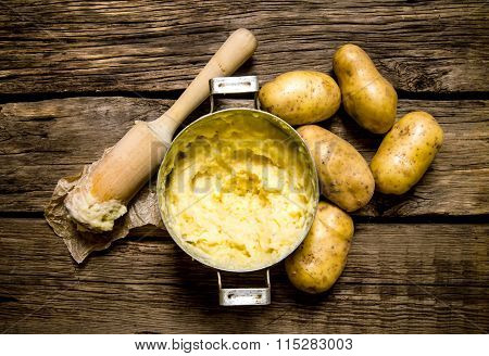 Cooking Mashed Potatoes With Pestle On Wooden Background.