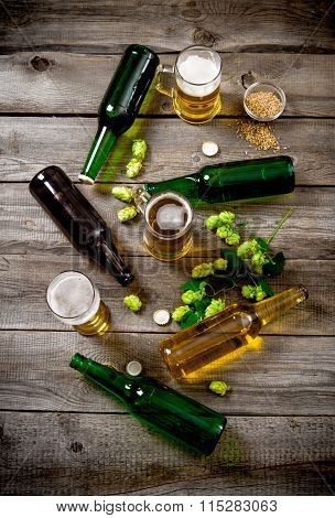 Bottles And Glasses Of Beer, Malt And Green Hops On A Wooden Table.