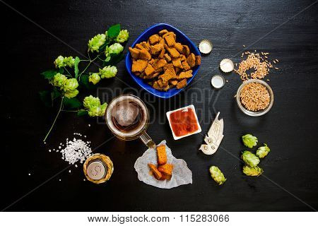 Beer Set. Glass Of Beer, Crackers, Ketchup, Salt. The Ingredients For Brewing: Malt And Hops. On A W