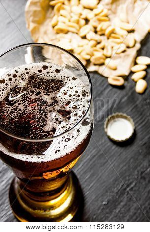 Beer With Peanuts On The Black Wooden Table.