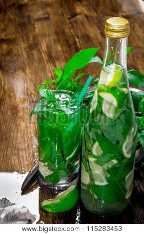 Mojito Cocktail. Freshly Made Mojito In Glass And The Bottle With Mint And Lime, Sugar And Rum. On A