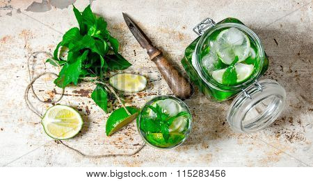 Ingredients For Making Mojitos - Lime, Mint Leaves, Rum, Citrus Knife And An Old Table.