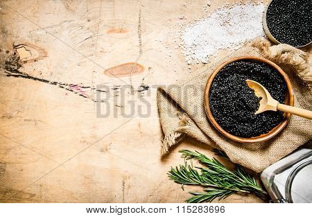 The Concept Of Black Caviar. Black Caviar In Cup With Salt And Rosemary.