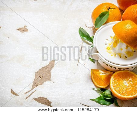 Squeezing Juice From Fresh Oranges . On Rustic Background.