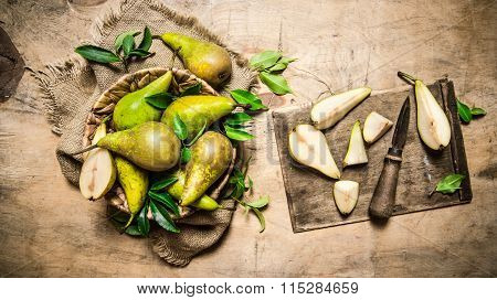 Cut Fresh Pears On Old Cutting Board, With A Basket Full Of Pears.