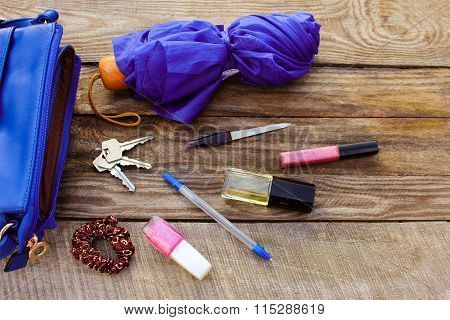 Blue women's purse, umbrella and women's accessories. Things from open lady hand bag.