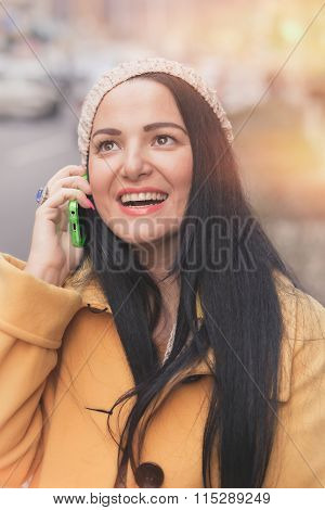 Woman using cell phone on city street. Beautiful  woman talking on cell phone while walking down cit