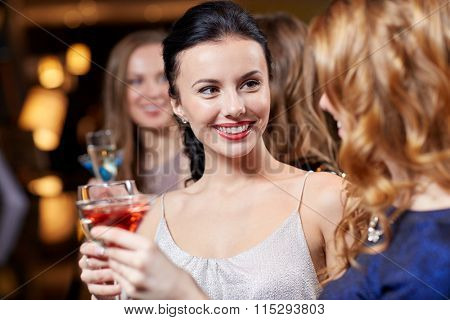 happy women with drinks at night club