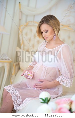 Happy Pregnancy, Waiting For Baby. Pregnant Girl Sitting On A Bed With Baby Booties