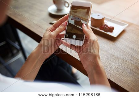 Female taking pictures with cell phone camera of delicious pastry during rest in cafe