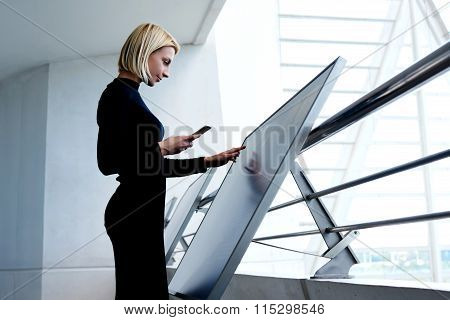 Smart businesswoman holding cell telephone while exploring project on interactive monitor