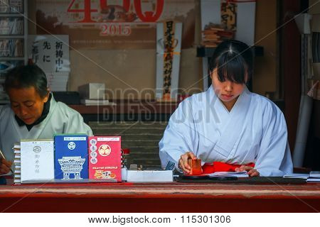 NIKKO, JAPAN - NOVEMBER 17, 2015: Miko - Japanese Priestess at Nikko Toshogu Shrine
