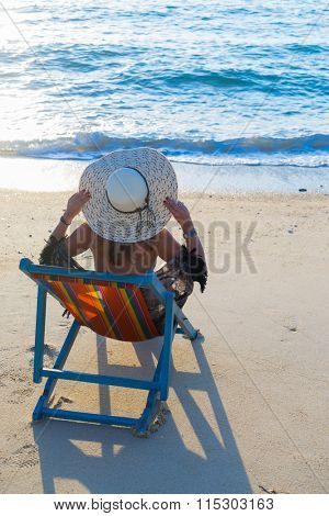Woman sitting on the lounge chair at the tropical beach