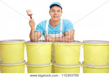 Young male decorator holding a paintbrush and posing behind a stack of color buckets isolated on white background