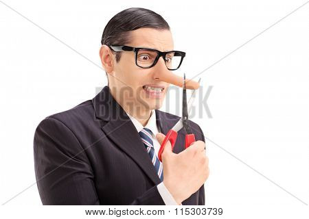 Worried businessman with long nose cutting the tip of his nose with scissors isolated on white background