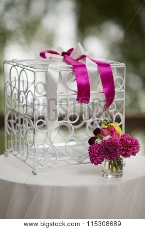 Vintage White Ornated Metal Cage At Wedding Aisle With Flowers In A Vase Closeup