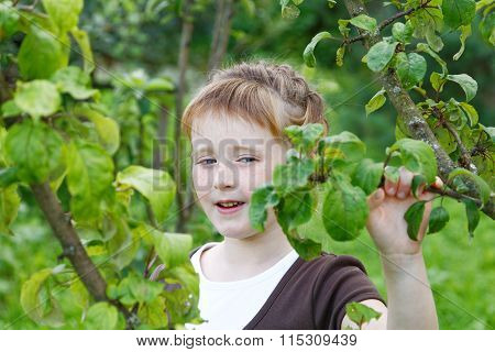 The Girl Winks One Eye Against Spring Foliage
