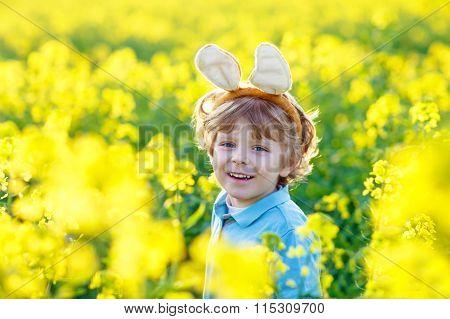 Little kid boy with Easter bunny ears in rape field