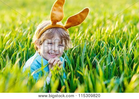 Adorable little boy with Easter bunny ears playing in green gras